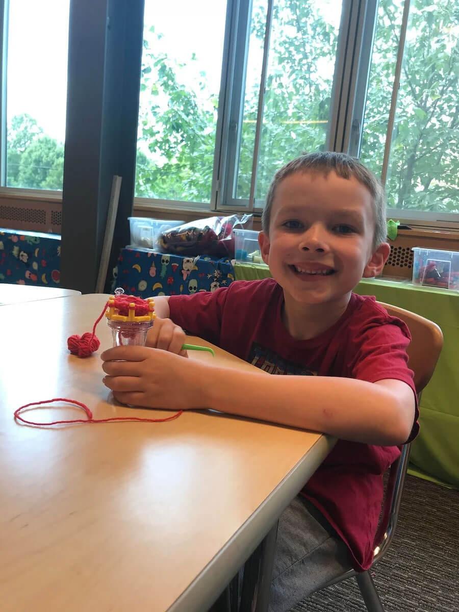 Child (boy) smiling with Wonder Knitter