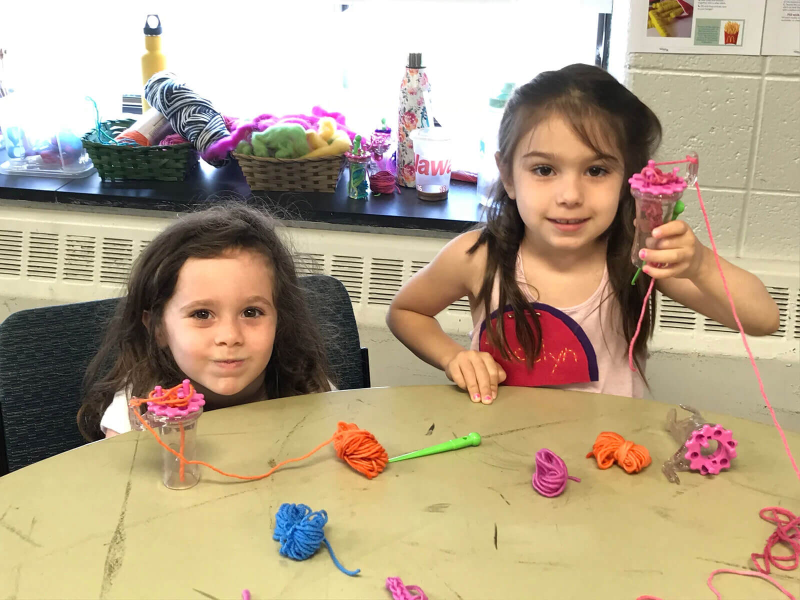 Two children (girls) smiling with Wonder Knitters
