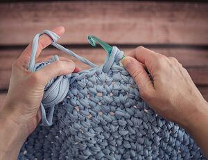 Hands crocheting with blue yarn and crochet hook