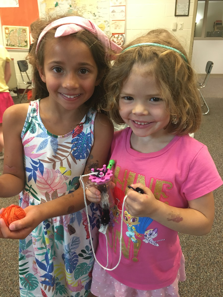 Two children (girls) smiling with knitting projects