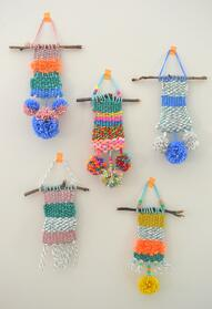 Five colorful weaving projects hung on wall by branches, pom poms