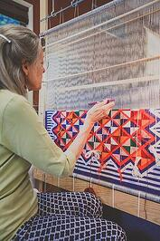 Woman weaving geometric pattern on upright loom