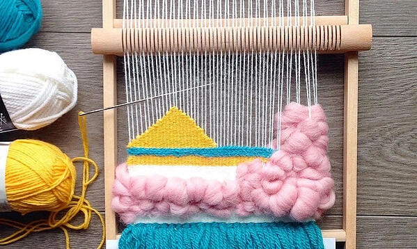 Yellow, blue, pink, and white weaving pattern on wooden loom